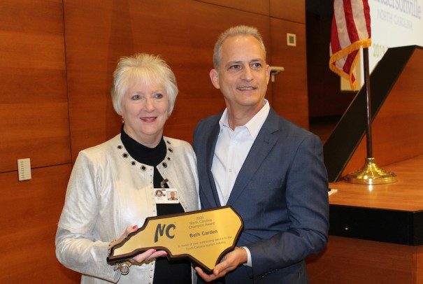 Henderson County Tourism Development Authority Director Beth Carden accepts North Carolina Champion Award from Visit NC Director Wit Tuttell.